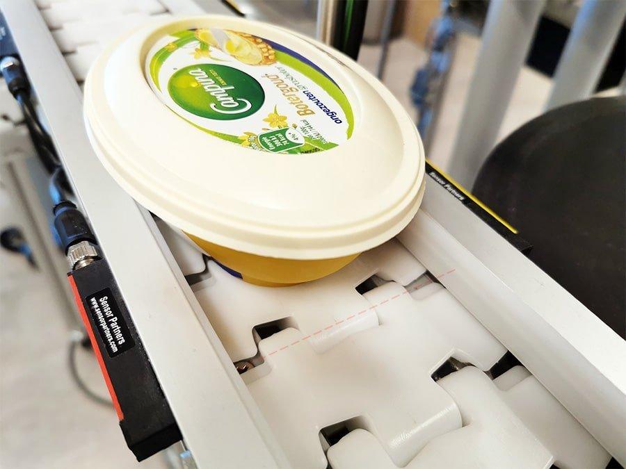 Onzichtbare detectie van productverpakkingen op een transportband met fotocellen van Telco Sensors